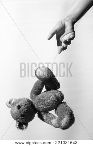 Black and white photo of a girl's hand throwing a teddy bear, theme of social problems