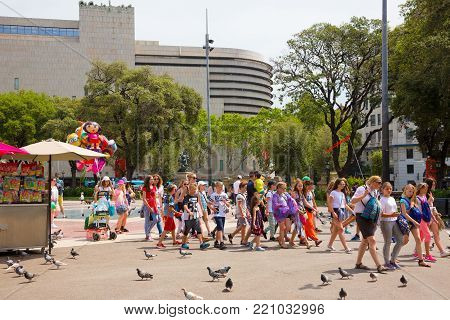 Barcelona, Catalonia, Spain - JUNE, 2016. Tour group of children with guide on The famous Plaza Catalunya in Barcelona in the summer