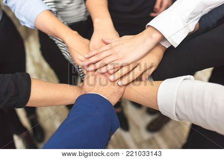 Above view of business partners hands on top of each other symbolizing companionship and teamwork