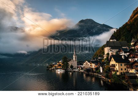 Scenic view of famous Hallstatt lakeside town reflecting in Hallstattersee lake in the Austrian Alps in morning light with bright clouds, Salzkammergut region, Austria