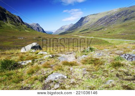 View of mountain ranges in the Scottish Highlands from Glen Coe Valley on a clear summer day