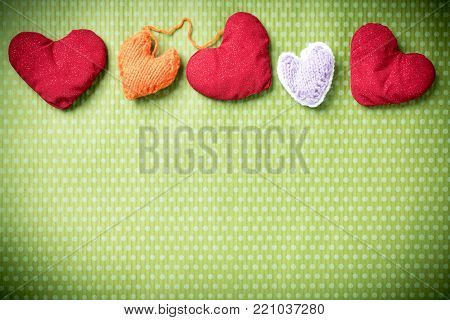 Valentines Day. Colorful knitted hearts on a vintage background in polka dots. Red heart. Green background. Valentine's day. Heart pendant. Valentine cards. Eighth of March. International Women's Day.
