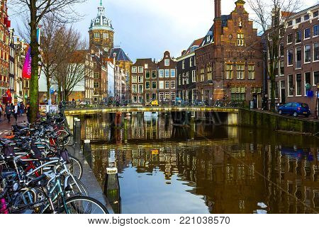 Amsterdam, Netherlands - December 14, 2017: The people going near most famous canals and embankments at Amsterdam, Netherlands on December 14, 2017. General view of the cityscape and traditional Netherlands architecture