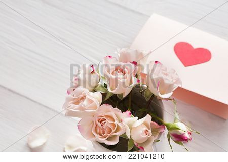 Valentine background with pink rose flowers bouquet and handmade greeting card on white rustic wood. Happy lovers day mockup, copy space, closeup