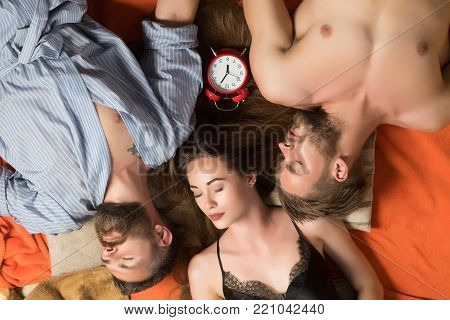 people lovers sleep at alarm clock, time. Love triangle and romance, perfect morning. Swinger relations, relax, wake up. men and woman with long hair, lover. Family trust, polygamy, betrayal. friends