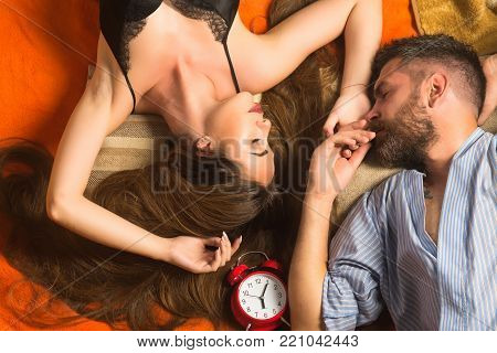 Relations, relax, wake up. Bearded man and woman with long hair, time. Happy family laying tired with clock, trust. Couple in love sleep on floor with alarm clock. Love and romance, perfect morning.