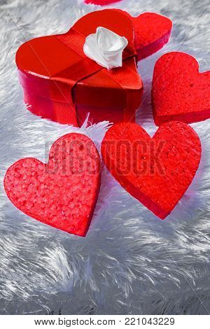 Gift box in the shape of a heart and tied with a red ribbon with a bow in the shape of a rose lies on the pillow faux fur surrounded by decorative hearts
