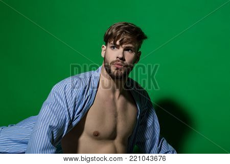 Spa, wellness, grooming. Man in blue dressing gown on green background. Macho with sexy torso in bathrobe. Home clothes, leisure wear. Fashion, style concept, copy space