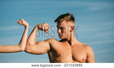 Bodybuilder with strong hand biceps, triceps contest with female hand on blue sky. Contrast, competition, conflict concept. Masculinity and femininity. Sport, fitness, strength