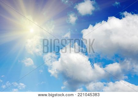 Bright sun in the clouds on the blue sky