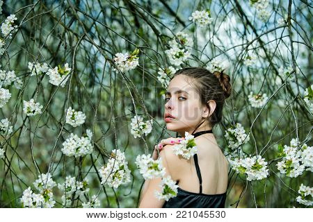 Woman or girl with no makeup face skin pose in trees with blossoming flowers on spring day on floral environment. Beauty, youth, flourishing, growth concept