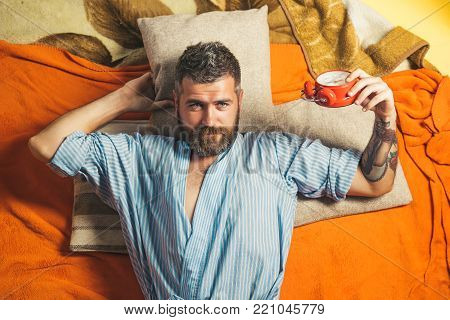 Bearded man sleep on floor with alarm clock. Time management, perfect morning. Relax and wake up, time. Man with clock in bedroom, loneliness. Tired hipster with clock.