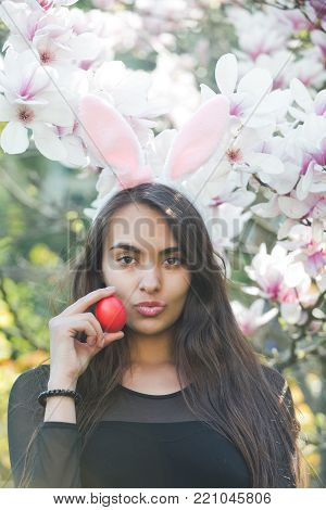 woman or adorable girl with sexy, plush lips and rosy bunny ears on long, brunette hair holding red egg at blossoming, magnolia flowers, trees, garden on floral background. Easter. Spring