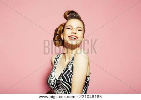 Woman with retro hair and fashionable makeup, pinup. Girl in stylish vintage dress on pink background. Makeup, hairdresser and cosmetics. Beauty and fashion, cosmetics. pinup, youth and look.