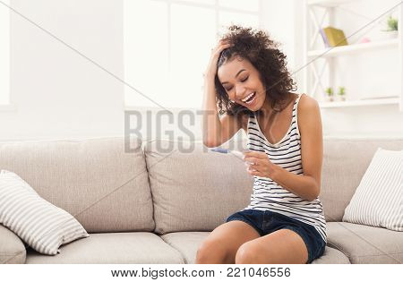 Smiling and excited african-american girl checking her recent pregnancy test, sitting on beige couch at home, copy space