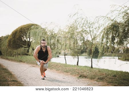 Running in the park. Active sport concept. Healthy sportsman does exercises on the street. Tired athlete in sportswear get a pause.