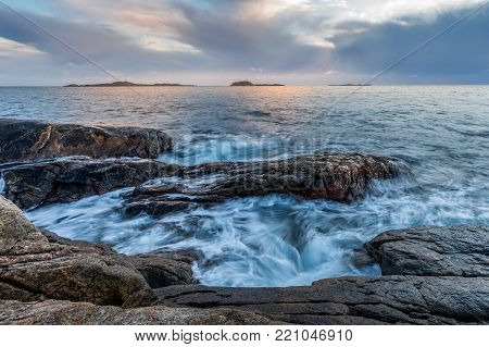 Waves at the shore in Helleviga recreation area, cloudy sky and blue hour, evening light and long exposure. Helleviga, Norway, Europe.