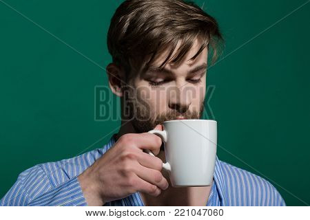 Breakfast, coffee or tea time. Man with cup on green background. Morning routine concept. Bachelor in blue dressing gown with mug. Hot drink, diet, health.