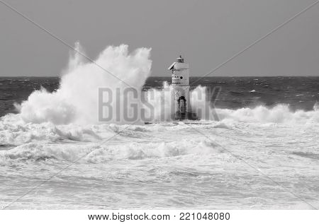 White lighthouse on the cliff. Lighthouse Mangiabarche situated in the south of Sardinia. Italy. Black and white, grey sky, white wave.