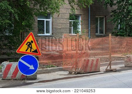 Repair work. Road repair in city street. City street construction site with barricades, safety fence net, road work and detour signs.