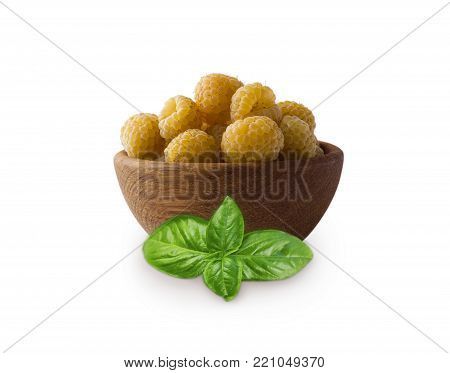 Raspberries in a wooden bowl with basil isolated on white background. Vegetarian or healthy eating. Juicy and delicious yellow raspberry with copy space for text.