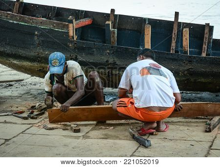 Varanasi, India - Jul 12, 2015. People working with wooden boat in Varanasi, India. Varanasi is the holiest of the seven sacred cities (Sapta Puri) in Buddhism, Hinduism and Jainism.