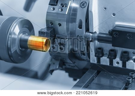 The CNC lathe machine cutting the thread of the pipe.