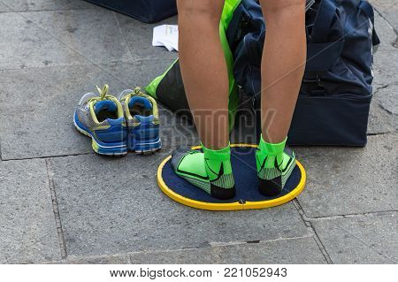Young Man Changing Shoes on Foot Mat in City Street Before City Marathon.