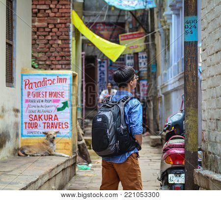 Varanasi, India - Jul 12, 2015. A young man walking on street in Varanasi, India. Varanasi is the holiest of the seven sacred cities (Sapta Puri) in Buddhism, Hinduism and Jainism.
