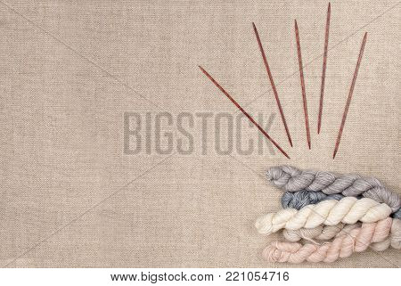 Pastel colors hank of yarn and wooden knitting needles on canvas background with space for text.
