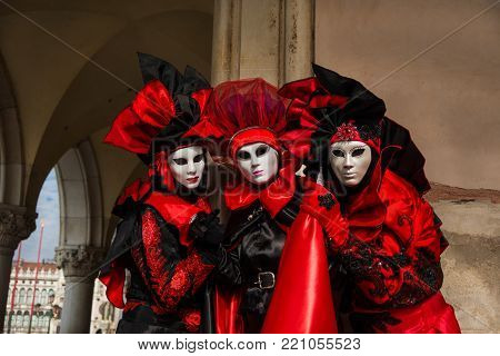 VENICE, ITALY - FEBRUARY 27: Three Venice Carnival Masks with Doge Palace and Saint Mark Square in the background February 27, 2017 in Venice, Italy