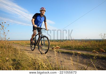 Male Cyclist Driving Rural Dirt Road Outdoors