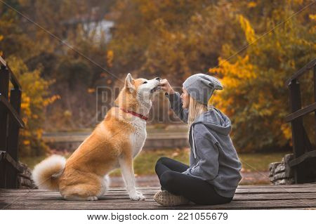 Young woman with her Akita inu dog in nature.