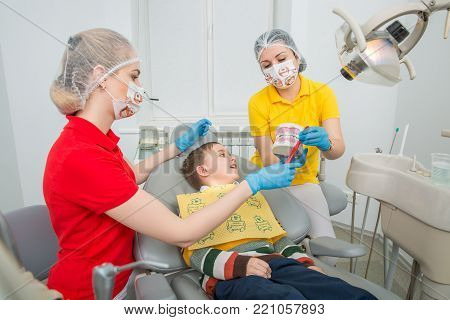 the dentist with assistent showing the little boy how to clean the teeth with a toothbrush on an artificial jaw dummy. Madical office