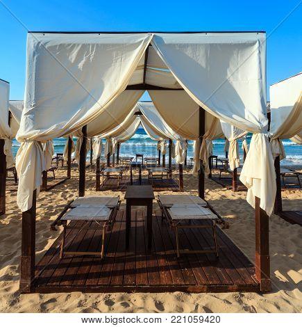 Luxury beach tents canopies on morning paradise white sandy beach ( Salento, Puglia, south Italy).The most beautiful sea sandy beach of Apulia.
