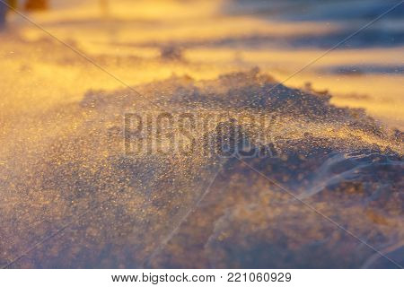 Snow background in close up. Surface of fresh winter snow in sunset light. snow-covered at sunset snowstorm, sunset snow blizzard