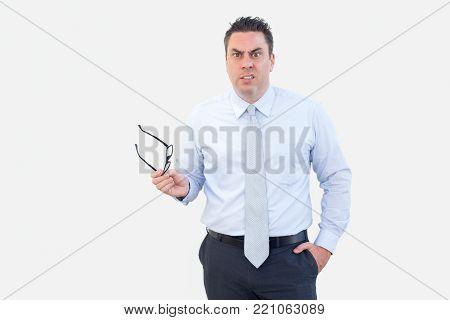 Closeup portrait of indignant middle-aged man looking at camera and holding glasses. Discontent concept. Isolated front view on white background.