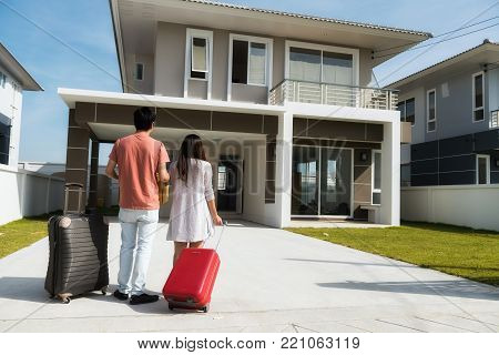Happy smile young Asian couple holding Mock up home model while sitting on their new house with many moving boxes and luggage at empty master bedroom.