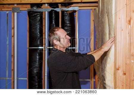 Construction worker thermally insulating house attic with glass wool installation of insulation in the house insulation of the house