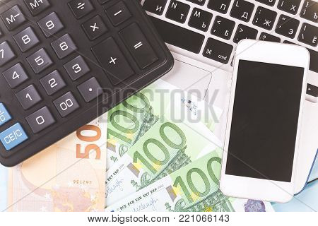 Business concept. Working desk with laptop, calculator, clock, phone and euro bank notes money. Close up image.