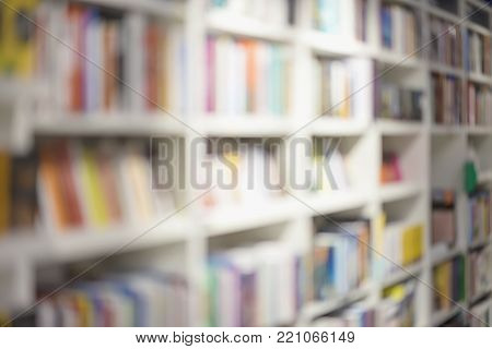 Abstract blurred bookshelves with books, manuals and textbooks on bookshelves in library or in bookstore, for backdrop. Concept for education, reading
