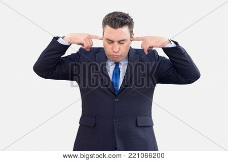 Concentrated male employee focusing on problem. Serious tired businessman covering ears with fingers to not listening to loud sound. Displeased man plugging ears because of noise. Hear no evil concept