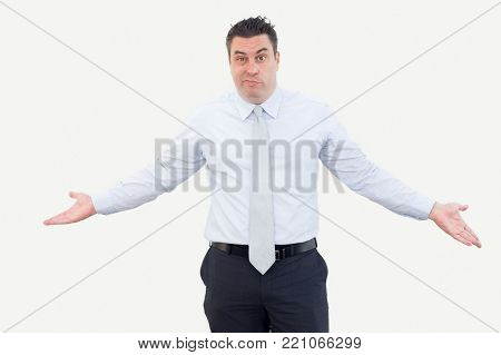 Discombobulated businessman shrugging arms because of uncertainty. Serious expressive handsome male manager puzzled with business news looking at camera. Misunderstanding concept