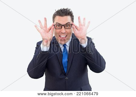 Excited amazed businessman shocked with news and adjusting eyeglasses to read information. Surprised handsome male manager knowing news about sales. Astonishment concept