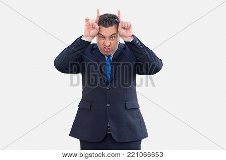 Furious expressive businessman showing horns and looking at camera. Angry stubborn handsome salesman forcing issues showing his character. Obstinacy concept
