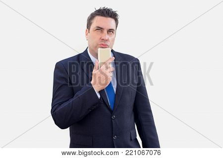 Pensive businessman thinking about text message and leaning head on smartphone. Introspective sales manager lost in thoughts reflecting about management strategy. Modern business concept