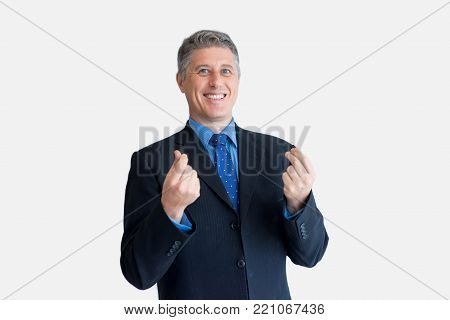Portrait of cheerful mature Caucasian businessman wearing black jacket and necktie smiling at camera and showing money gesture. Benefit and advantage concept
