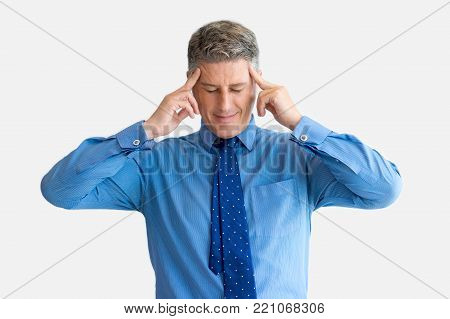 Portrait of stressed or concentrated mature Caucasian businessman wearing blue shirt and necktie suffering from migraine. Exhaustion and overworking concept