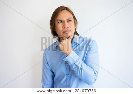 Serious young Asian man with hand on chin staring into vacancy. Student concerned about exams. Challenge or concerning concept.