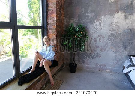 Sweet woman in excellent spirits and with smile on face poses and sits on windowsill near high panoramic window in spacious stylish bedroom with gray walls, bed and orange tree. girl of European appearance and gathered hair dressed in blue blouse with ruf